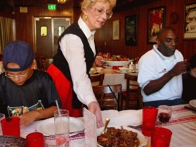 Louis' Basque Corner restaurant waitress serving traditional Basque meat, family style (photo EuskalKultura.com)