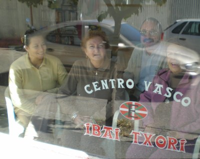 The president and some of the members of the Board of Ibai Txori at the other side of the glass of their headquarters in Concepcion del Uruguay (photo EuskalKultura.com)