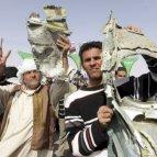 Rebeldes opositores libios celebran mientras muestran un trozo del fuselaje de un casa del ejército libio.