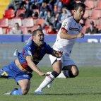Juanfran García (i), cae al suelo en su lucha por el balón con el centrocampista iraní del Osasuna, Masoud.