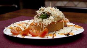 CAPRICHO ITALIANO:  Sobre rodaja de pan, queso emmental y pimiento italiano, todo ello enrollado en rodaja de calabacín y jamón serrano, aderezado con salsa de piquillo.