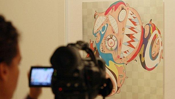 Una reportera gráfica capta imágenes de una de las litografías de la exposición de Takashi Murakami que hoy se inaugura en Donostia.