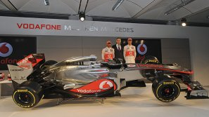 Los pilotos británicos de Fórmula Uno Lewis Hamilton (izq) y Jenson Button (dcha) y el director del equipo McLaren, Martin Whitmarsh (c) presentan el nuevo monoplaza MP4-27 de McLaren en el Centro Tecnológico de McLaren en Woking (Reino Unido).