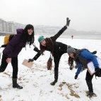 Tres jóvenes disfrutan de la nieve en la playa de La Concha, cubierta por un manto blanco tras la nevada que se registró ayer por la mañana en Donostia