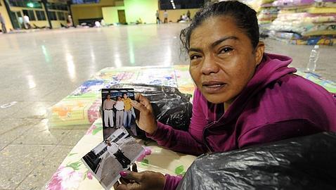 Una mujer muestra fotos de su hijo, muerto en el incendio