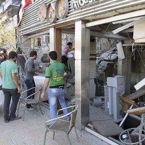 Varias personas inspeccionan un local tras un acto terrorista.
