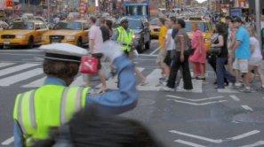 Un agente regula el tráfico mientras los neoyorquinos caminan por Times Square.