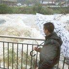 Dos jóvenes observan la crecida del rio Galindo a su paso por la localidad vizcaína de Alonsotegi