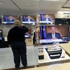 Varias personas siguen desde las televisiones de unos granes almacenes la intervención del Rey