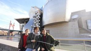 Tres jóvenes turistas recurrieron a su 'brazo' para hacerse un autorretratro ayer ante el Guggenheim.