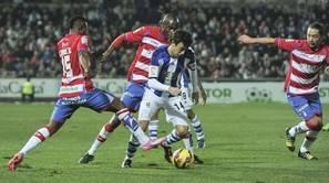 El centrocampista de la Real Sociedad Rubén Pardo (c) controla el balón rodeado de jugadores del Granada.