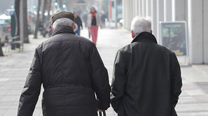 Dos hombres de edad avanzada caminan por las calles de Pamplona.