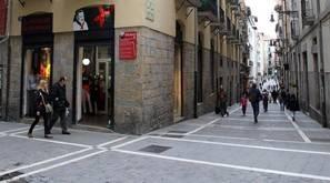Varias personas pasean por la parte antigua de Pamplona.