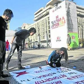 Jóvenes seguidores de Syriza pintan ayer un cartel en Atenas.