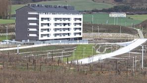 Bloque de viviendas ya entregado, junto a una de las balsas de retención (zona verde), y los rediles en primer plano.