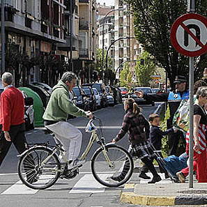 Ciclistas y peatones cruzan un paso de cebra, vigilados por un agente de la Policía Local de Burlada.