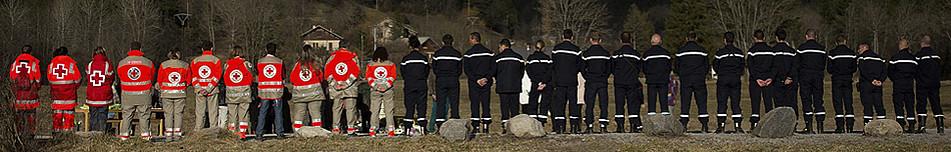Voluntarios de la Cruz Roja y agentes de la Gendarmería francesa, ante el monumento en memoria de las víctimas del accidente del avión A320.