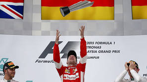 Sebastian Vettel lanza su trofeo ante la mirada del segundo clasificado Lewis Hamilton (i) y el tercero, Max Verstappen.
