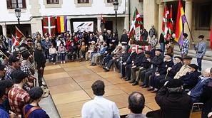 Gudaris y familiares de represaliados, sentados en la plaza de Elgeta rodeados por los actores de la recreación que se hizo ayer en Intxorta minutos antes.