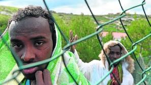 Inmigrantes llegados a Lampedusa son conducidos al centro de internamiento.