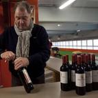 Un hombre descorcha un vino de Rioja Alavesa, con etiqueta de Rioja, en una feria.