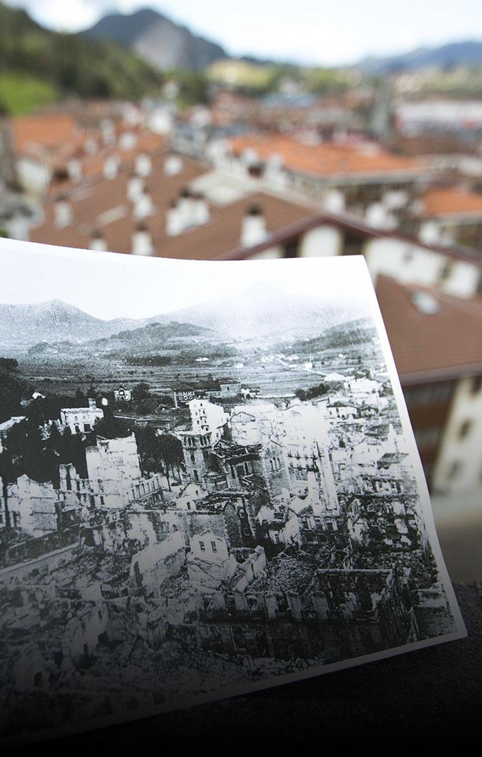 Esku anonimo batek bonbardaketaren argazkia eusten du 2016ko Gernikaren aurrean