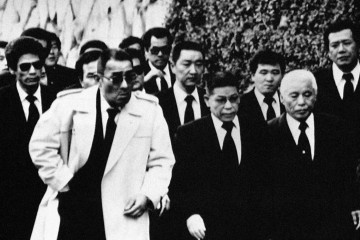 Top members of the Yamaguchi-gumi Japan's largest Yakuza Organization, arrive for the funeral in Kobe, western Japan on Dec. 16, 1988, for their boss Masahisa Takenaka, who was killed by a splinter group's gunman in February 1985. Soon after Takenaka's death the gang went to a war to avenge the murder, which has left 25 dead and 70 injured by police count, now seems to be nearing an end. (AP Photo)