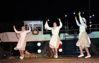 "Dantzaris from Trenque Lauquen dancing in front of the boat in the ""Immigrant"" show"